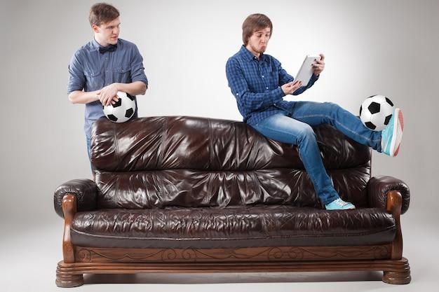 Портрет двух парней с мячами на диване на сером фоне