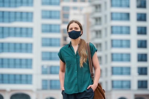 의료 얼굴 마스크에있는 여자의 초상화는 걷는 동안 바지 주머니에 손을 밀고있다