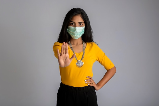 Портрет женщины с медицинской маской показывает знак остановки руками. концепция здравоохранения и медицины