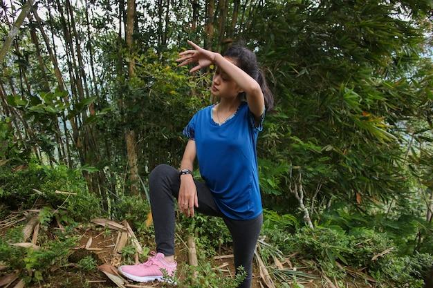 彼女が疲れを感じた運動をしている若いアジアの女性の肖像画