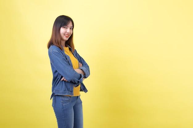 無地の黄色に対してスタジオで若い、キュートでアスリートのタイのアジアの女の子の肖像画