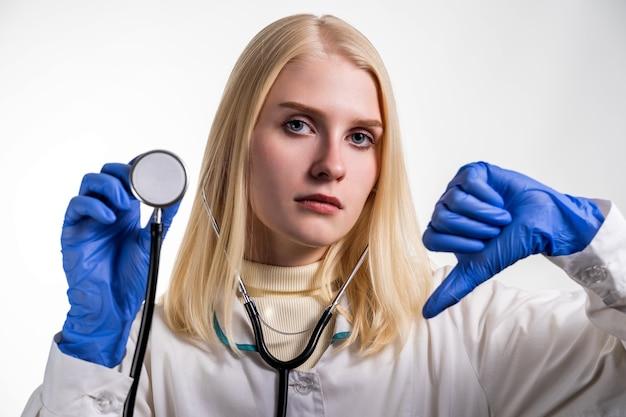 Портрет молодой женщины-интерна со стетоскопом в правой руке и направленным вниз