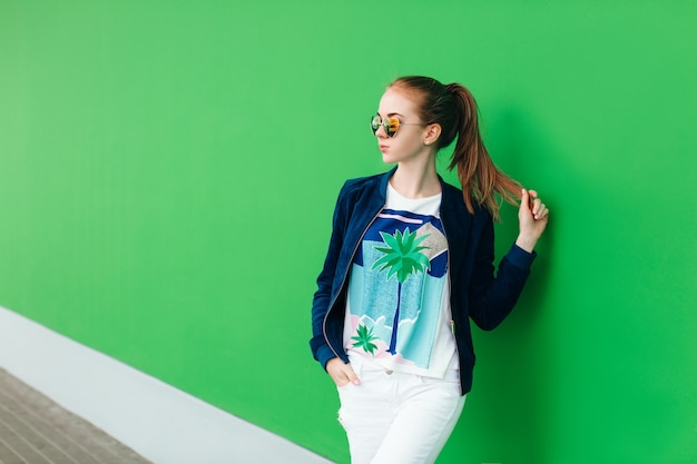 Портрет молодой девушки на улице возле зеленой стены с белой линией вниз. девушка носит солнцезащитные очки, держит в руке хвост и смотрит вдаль.