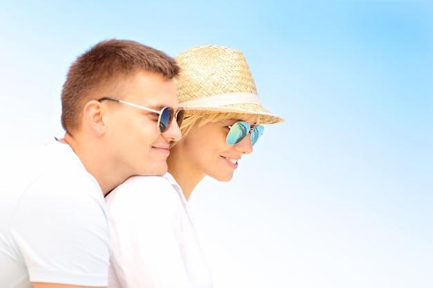 青い空の上の若い幸せなカップルの肖像画