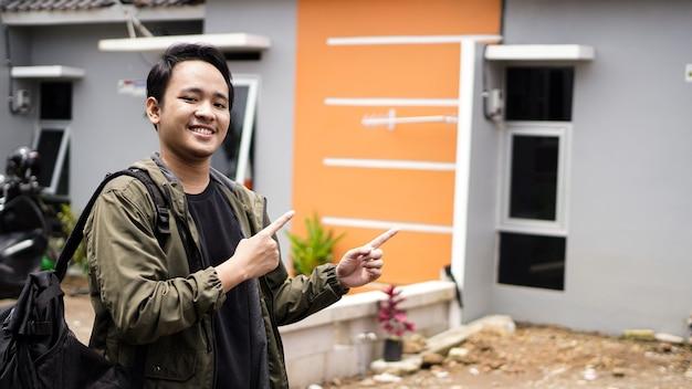 彼らの新しい家の前に立っている若い男の肖像画
