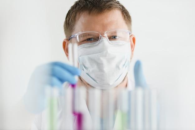 若い外科医の化学者の医師の肖像画は青い液体の入った容器を見ており、マスクはウイルスと病気に対するワクチンのワクチンと戦っています。 Premium写真
