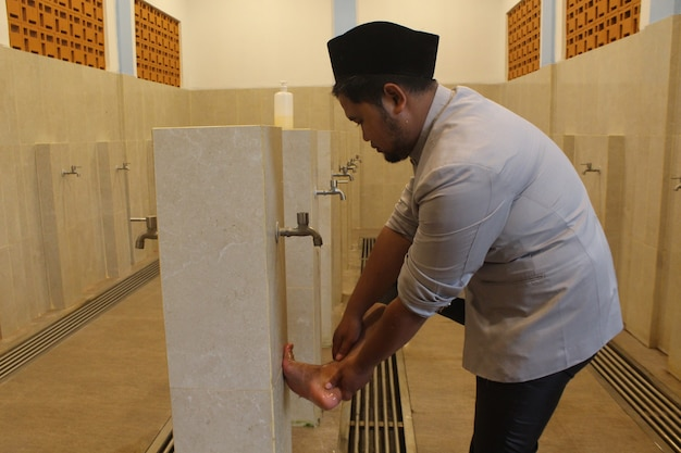 Портрет азиатского мусульманина, совершающего омовение в мечети перед молитвой