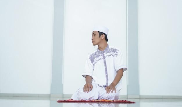 Портрет азиатского мусульманина, который молится в мечети, молитва называется шолат, относится к концу шолата.