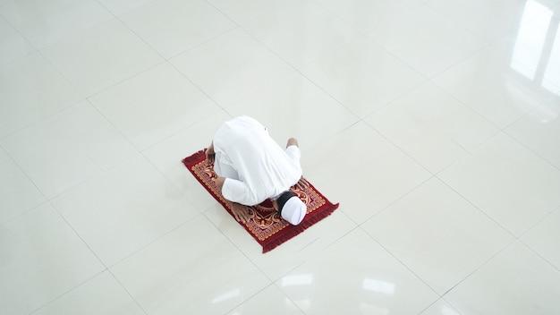 Портрет азиатского мусульманина молиться в мечети, молитва называется шолат, движение суджуд на шолате