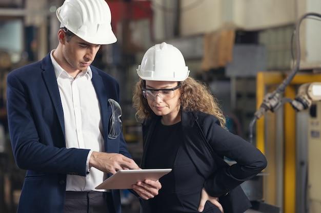 工場でタブレットを持って働いている産業の男性と女性のエンジニアの肖像画。