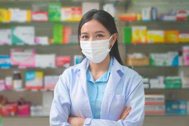 現代の薬局ドラッグストアでサージカルマスクを着用しているアジアの女性薬剤師の肖像画