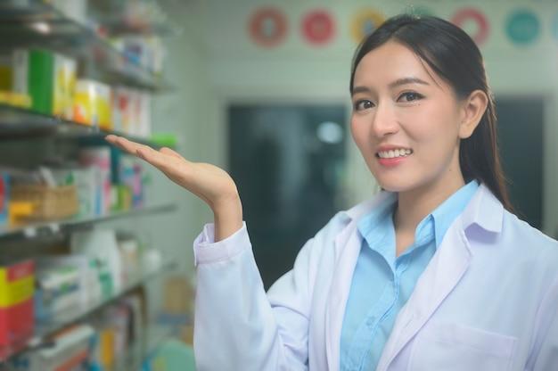現代の薬局ドラッグストアで白衣を着ているアジアの女性薬剤師の肖像画