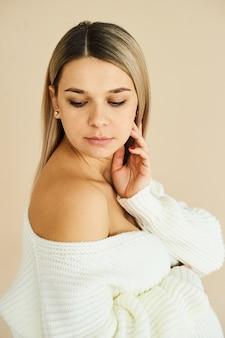 Портрет красивой беременной девушки, одетой в белый свитер на бежевом фоне