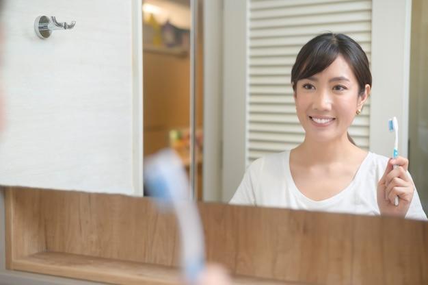 Портрет красивой молодой женщины, держащей зубную щетку с пастой