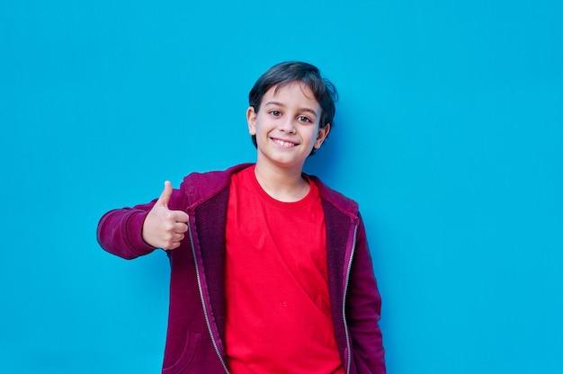 Портрет мальчика в футболке и куртке с большим пальцем правой руки вверх