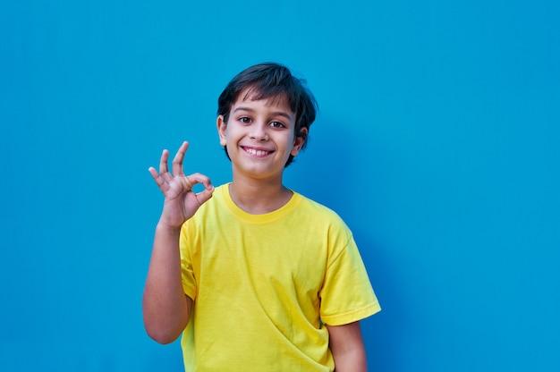 Портрет мальчика в желтой футболке, делая жест рукой