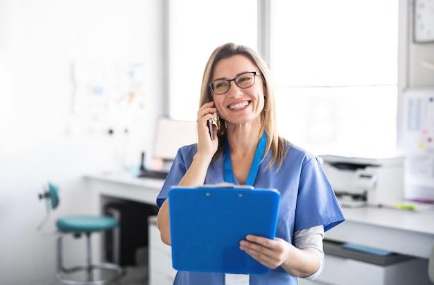 스마트폰을 사용하여 현대 치과 수술에서 쾌활한 치과 조수의 초상화.