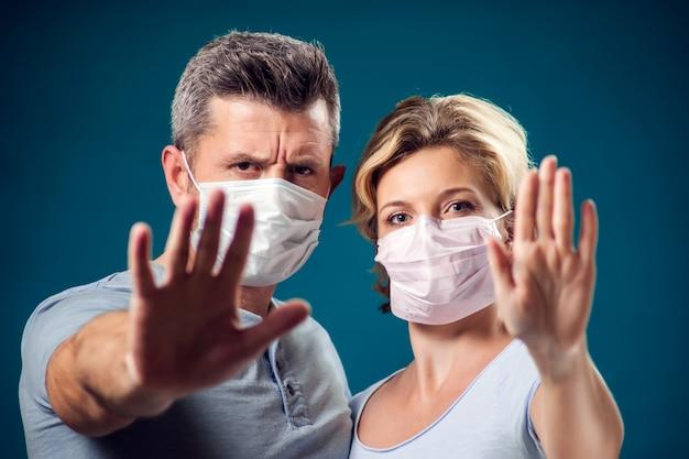 ストップジェスチャーを示す顔医療マスクを持つ男女のカップルの肖像画。人、医療、医学のコンセプト