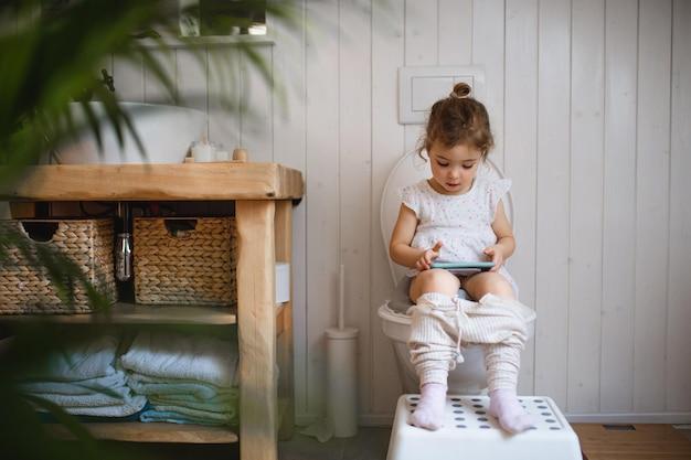 Портрет милого маленького сидящего на туалете в помещении дома, используя смартфон.