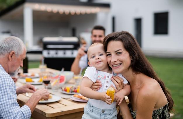 庭のバーベキューで屋外のテーブルに座っている拡大家族の肖像画。