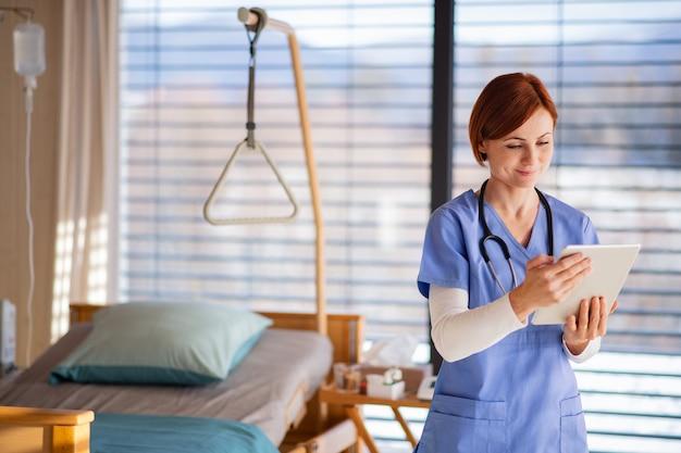 タブレットを使用して、病室に立っている女性の医師または看護師の肖像画。