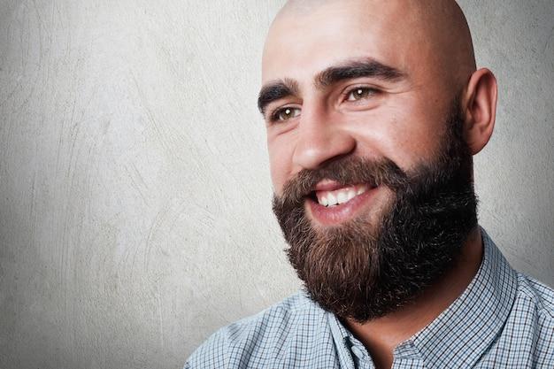 厚いひげと口ひげが誠実な笑顔を持つハンサムなハゲ男の肖像