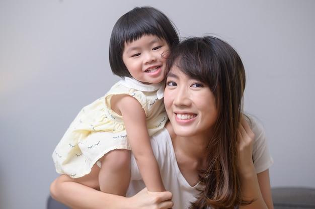 幸せなアジアのママと娘の肖像画