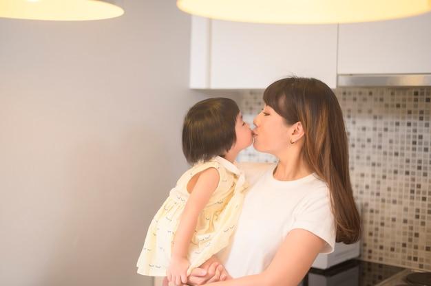 自宅のキッチンで幸せな母と娘の肖像画