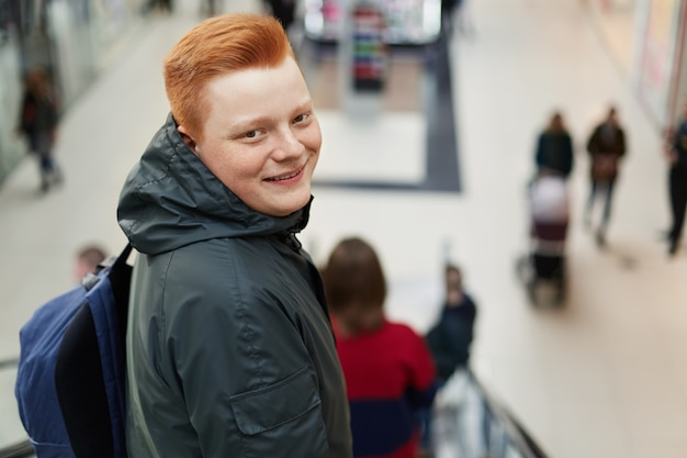 ショッピングモールに戻って立っている赤い髪の幸せな若い魅力的なヒップスターの肖像画