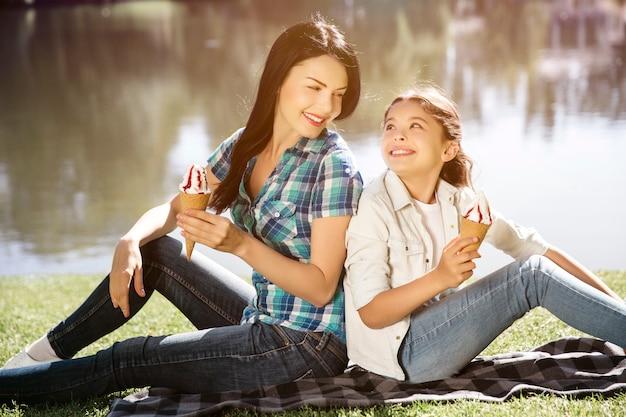 Портрет красивых и привлекательных девушек, сидящих спиной к спине и смотрящих друг на друга. они держат два минуса мороженого и улыбаются.