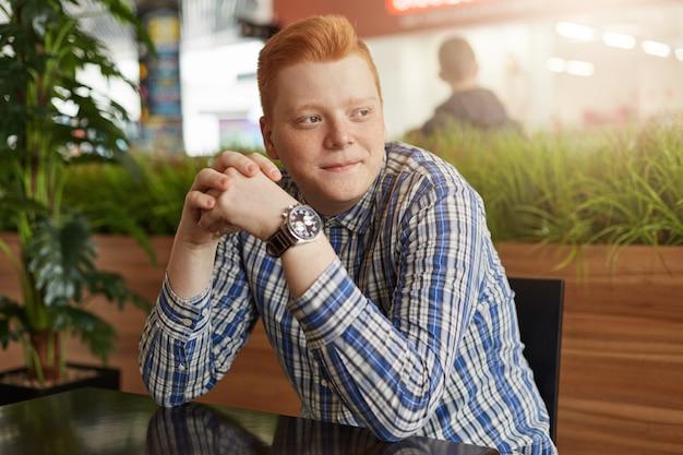 Портрет рыжего мужчины с веснушками в стильной клетчатой рубашке и часах, сидя в уютном кафе в ожидании друзей Premium Фотографии