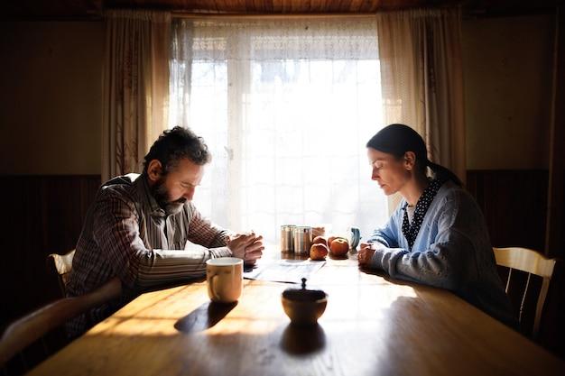 집에 있는 탁자에서 기도하는 슬프고 가난한 성숙한 부부의 초상화, 빈곤 개념.