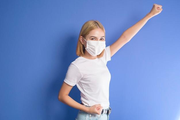 スタジオでサージカルマスクを身に着けている短いブロンドの髪の女性の肖像画