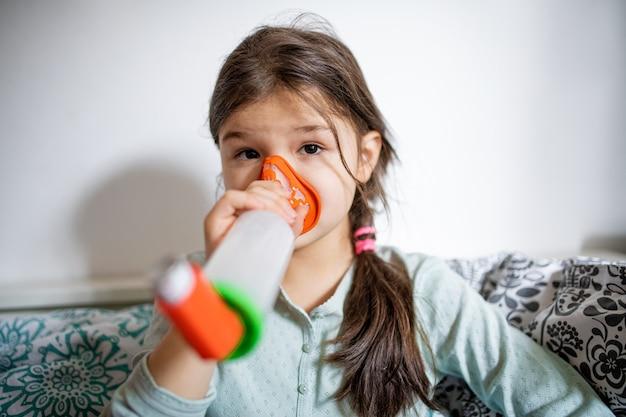 Портрет больной маленькой девочки дома, используя ингалятор.