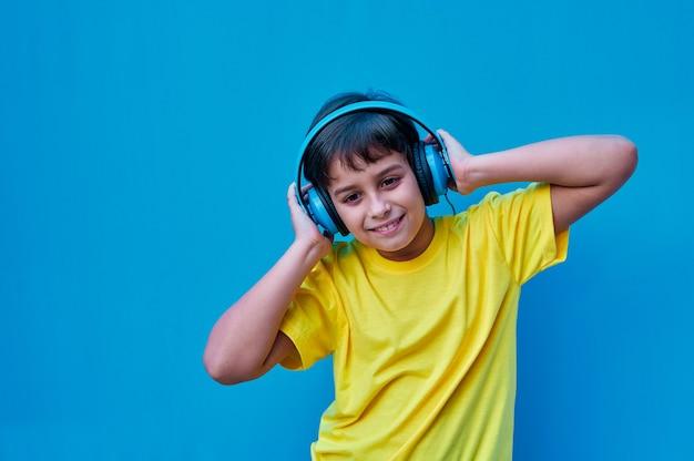 Портрет улыбающегося мальчика в желтой футболке и синих наушниках, слушающего музыку