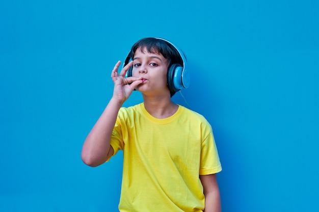 Портрет улыбающегося мальчика в желтой футболке и синих наушниках, делающий очень хороший жест