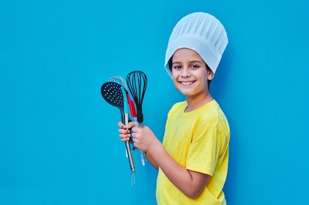 Портрет улыбающегося мальчика в желтой футболке и шляпе от шеф-повара с кухонной утварью, готовой научиться готовить