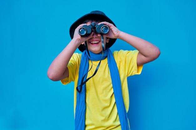 쌍안경을 통해 카메라를보고 노란색 티셔츠에 웃는 소년의 초상화