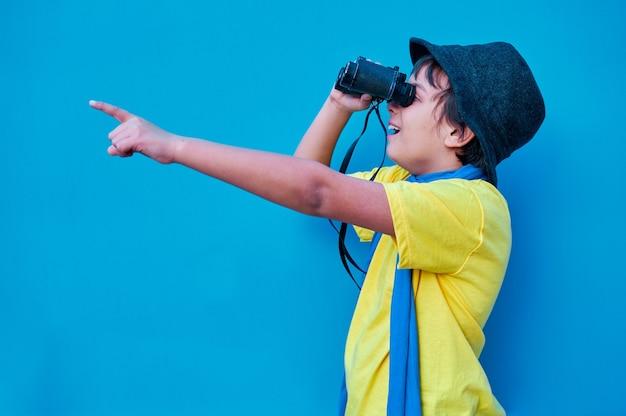 쌍안경을 통해보고 손가락으로 가리키는 노란색 티셔츠에 웃는 소년의 초상화