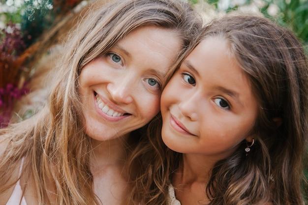 Портрет улыбающейся матери и ее дочери.