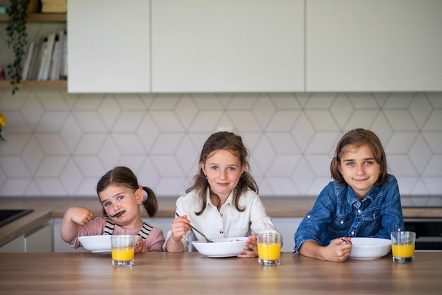 집에서 아침 식사를 할 때 카메라를 바라보는 세 여자 자매의 초상화.