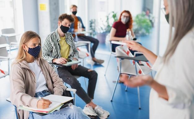 실내 교실에 있는 대학생의 초상화, 코로나바이러스, 그리고 정상적인 개념으로 돌아갑니다.