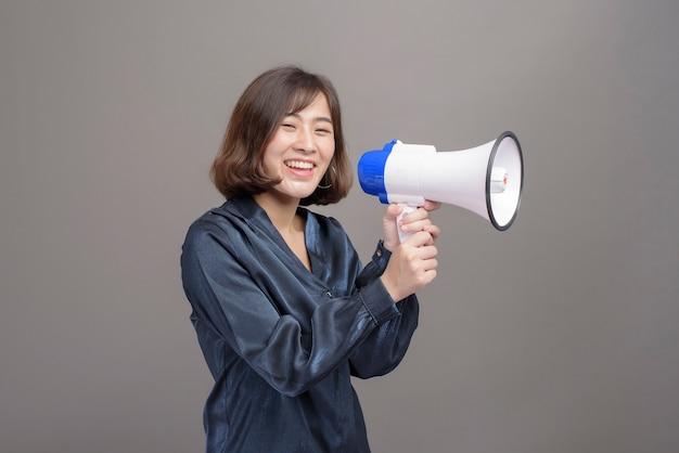 Портрет молодой красивой азиатской женщины, держащей мегафон на сером