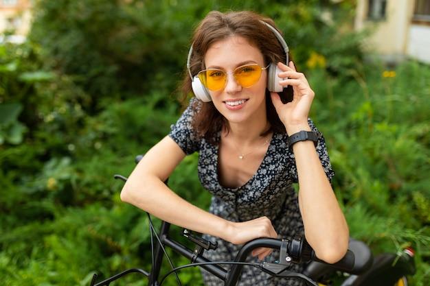 完璧な笑顔を持つ若い白人女性の肖像画、肉付きの良い唇、メガネ、イヤホン、自然の中を歩く、自転車に乗る