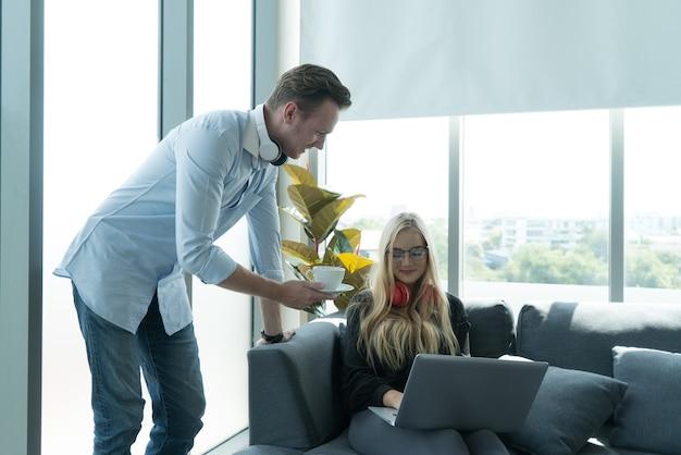 彼氏が自宅で現代の仕事のためにコーヒーを提供している間の若いカップルの肖像画