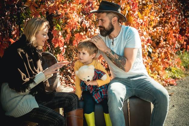 日没の甘いお母さんが彼女の息子に話しかける秋の自然の中で小さな子供を持つ若い家族の肖像画と...