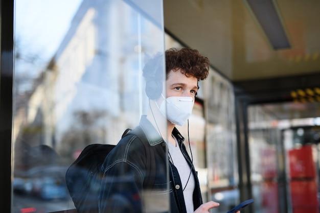도시의 야외 버스 정류장에 서 있는 젊은 통근자의 초상화, 코로나바이러스 개념.