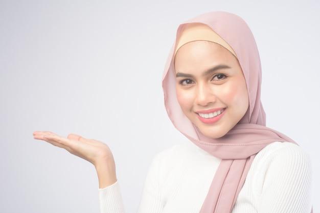 Портрет молодой улыбающейся мусульманской женщины в розовом хиджабе на белом фоне.