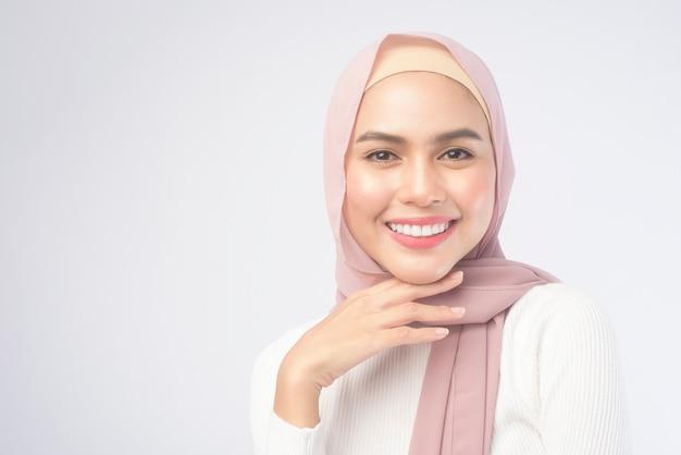 흰색 배경 스튜디오 위에 분홍색 히잡을 쓰고 웃고 있는 젊은 이슬람 여성의 초상화.