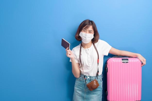 얼굴 마스크, 새로운 일반 여행 개념을 가진 젊은 여행자 여자의 초상화